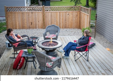 horizontal image of two caucasian ladies sitting in the back yard on a wooden deck around a fire pit  chatting.