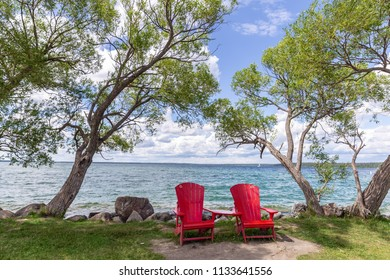 horizontal image of two empty deep red wooden chairs perched between two trees next to a big lake on a warm summer day.