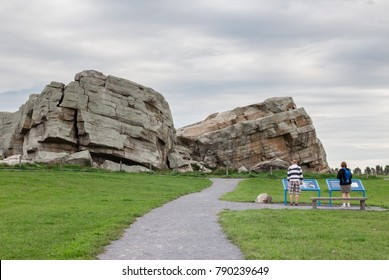 horizontal image of two people reading the information on a plaque of the glacial erratic-the big rock by Okotoks Alberta in the summer time