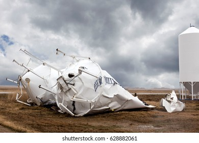 horizontal image of two steel granary bins lying crumpled and destroyed on the ground due to severe thunderstorms and wind under a very dark grey sky.
