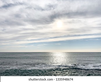 A horizontal image of the Tyrrhenian Sea in Ostia (Ostia Lido or Lido di Roma or Lido di Ostia) outside Rome, Italy on a cloudy winter afternoon with various shades of blue and a sky of clouds.