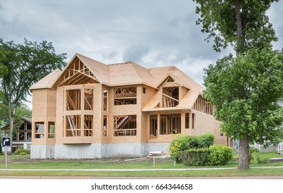 horizontal image of an unfinished big brand new home being built surrounded by many green trees in the summer time.
