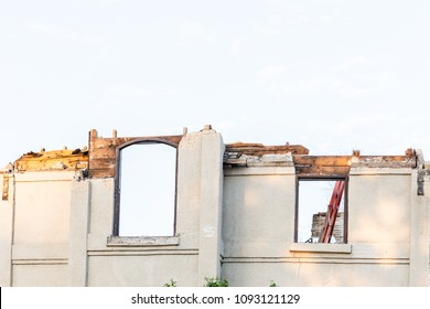 horizontal image of the upper half of an old stucco home with two windows and the roof  been torn off with copy space.