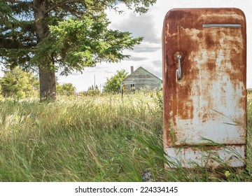 horizontal image of an very old rusted fridge sitting outside in the grass in the summer time.