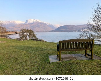 Horizontal image with view from a wooden bench over the great mountain Ben Nevis and Loch Linnhe in Corpach Village, near Fort William on the Scottish Highlands, Scotland.
