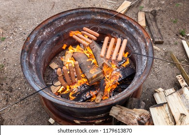 horizontal image of weiners being roasted on an open camp fire with wood lying beside.