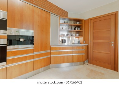 Horizontal image of well equipped modern kitchen in wood