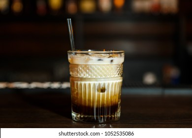 A horizontal image of a white russian cocktail in rocks glass in a bar.