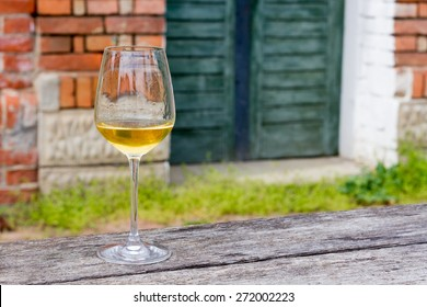 Horizontal Image of a wine glass with golden and little cloudy 2014 Chardonnay in it.Sharp focus on wine glass with blurred background and copy space on right