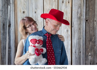 """horizontal image of  woman standing behind her man who is wearing cowboy hat and red tie with little white hearts embracing him holding  teddy bear with a valentine heart that says """"to the one I love"""""""