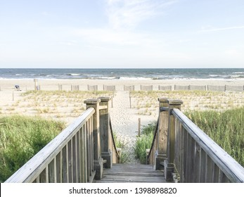 A horizontal image of a wooden walkway surrounded by long grass and sand dunes with steps leading to the beach and ocean in North Carolina.