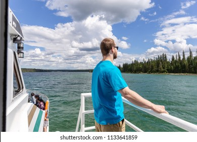 horizontal image of a young attractive  caucasian guy standing on the deck of a boat gazing across the lake while on vacation on a warm summer day.