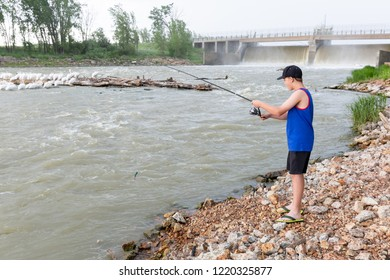 horizontal image of a young caucasian boy standing on the edge of the water by the dam fishing in the summer on a cloudy day.