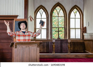 horizontal image of a young caucasian cowboy preacher holding the bible and preaching from his pulpit to his congregation in a country style rural church. - Shutterstock ID 1690483198