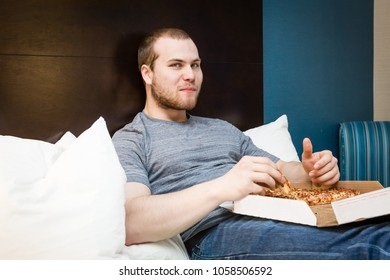 horizontal image of a young caucasian man sitting on a hotel bed eating a cheese pizza.