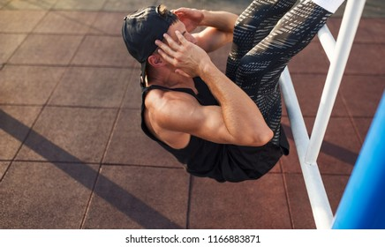 Horizontal image of young fitness man doing stomach workouts on horizontal bar outdoors. Side view of handsome athlete male model exercising outdoors, afternoon on sunset sunlight.
