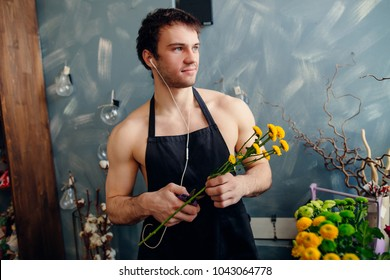 Horizontal Image Of Young Florist With Neked Body Listening To Music And Cutting Beautiful Mimosa Indoor