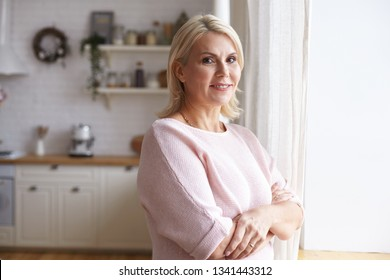 Horizontal indoor view of beautiful friendly looking European woman in her forties spending day at home, standing by window with arms crossed on her chest, having happy cheerful facial expression