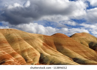 Horizontal landscape of the colorful Painted Hills in Oregon against cloudy blue skies.