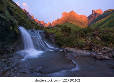 A horizontal landscape photograph of a beautiful waterfall in front of the Drakensberg escarpment mountains at sunrise with beautiful golden sunrise light on the cliffs in the distance.