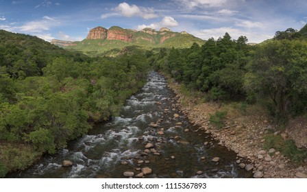 A horizontal landscape photograph of the Blyde River flowing away from the Blyde River Canyon at Swadini in Mpululanga, South Africa during a cloudy morning with mountain peaks in the background