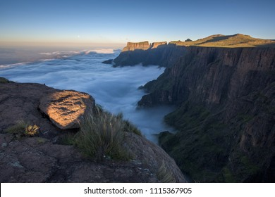 A horizontal landscape photograph of the Drakensberg Escarpment overlooking the Royal Natal Park, Devils Tooth and Eastern Buttress, during sunset with a cloud inversion building below.