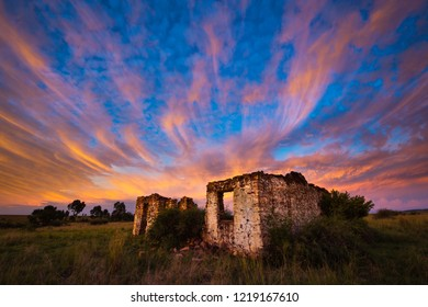 A horizontal landscape photograph of an old ruined farm house underneath a beautiful sunset sky.
