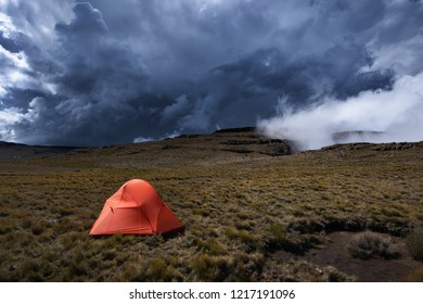 A horizontal landscape photograph of an orange tent set up on a mountain in the Drakensberg with an approaching storm in the background.