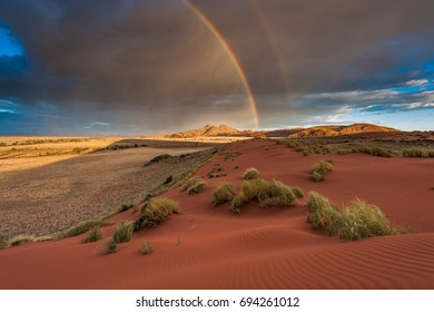 A horizontal landscape photograph of a rainbow across the Namibian Desert and mountains during a passing storm in the afternoon in Namib Rand, Namibia.