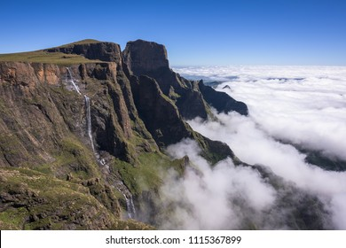 A horizontal landscape photograph of the Tugela Falls falling over the escarpment edge in the uKhahlamba Drakensberg Park in South Africa. A cloud iversion sits below and blue sky overhead.