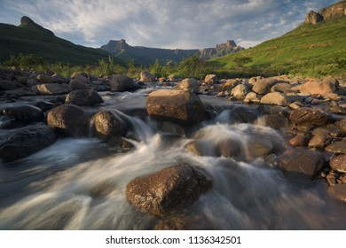 A horizontal landscape photograph of the Tugela River flowing over rocks during sunrise with clouds overhead at Royal Natal National Park in South Africa
