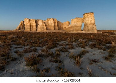 A horizontal landscape photography image of Monument Rocks in Kansas before sunset.  They are also known as Chalk Pyramids.