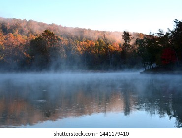 Horizontal landscape of a small lake at Devil's Den State Park in Arkansas. Light from the sunrise starts to burn off the mist. Ozark image