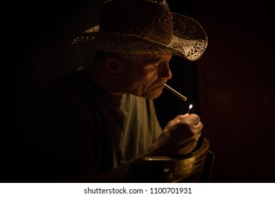 horizontal low key head shot of a caucasian rugged looking man lighting a cigarette with the flame lighting his face with copy space.