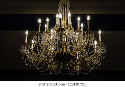 horizontal low key image of a beautiful antique vintage style chandelier covered with hanging beads and candle style lights all lit up with a dark background