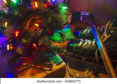 horizontal low key image of a Christmas tree with lights with a pair of black skates and hockey stick beside it