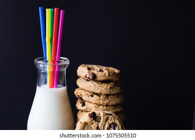 horizontal low key image of a glass milk bottle with milk and coloured straws with a stack of chocolate oatmeal cookies beside it on black background with room for text.