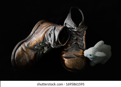 horizontal low key image of a pair of bronzed little boys shoes with a little white ornamental rabbit sitting beside them on a dark black back ground with copy space