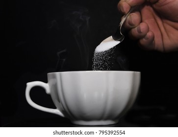 horizontal low key image of a teaspoon of granulated sugar being poured into a steaming hot cup of coffee.