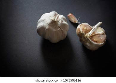 horizontal  low key image of a whole organic garlic bulb  and segments lying on a black background.