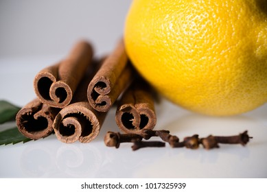 horizontal macro image of fresh lemon, cinnamon stick, whole cloves and bright green leaves, selective focus