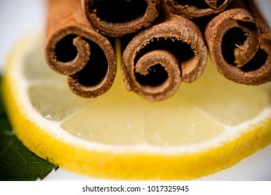 horizontal macro image of fresh lemon, cinnamon stick and bright green leaves. Selective focus.