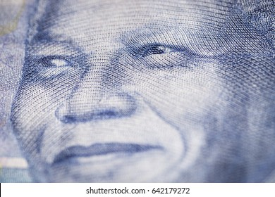 Horizontal marco detail of the image of Nelson Mandela in the obverse of South African ZAR banknote with a denomination of 100 rand.