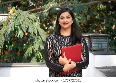 Horizontal medium portrait shot of modern successful Indian woman wearing body-hugging dress standing on terrace holding red folder with papers