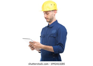 Horizontal medium portrait of successful handsome young adult Caucasian construction engineer wearing uniform using digital tablet, white background