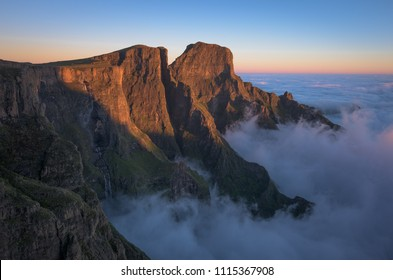 A horizontal mountain escarpment landscape photograph of the uKhahlamba Drakensberg Park at the Tugela Falls at sunrise with a heavy cloud inversion below, in South Africa.