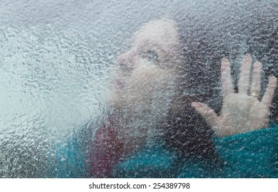 horizontal orientation of an attractive woman looking out through a window covered with thick ice, with her hand at the window / Memory Loss