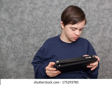 horizontal orientation of a boy with autism and down's syndrome sitting down, holding a tablet device in both hands as he looks at the screen / Apps for Visual Learners