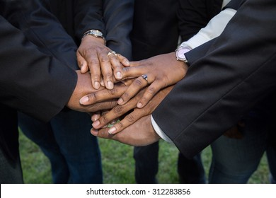 horizontal orientation close up of adult hands, wearing suits and business attire, stacked on one another in a show of unity and teamwork / Building Teamwork and Trust