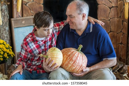 horizontal orientation close up of a boy with autism and down's syndrome and his smiling Dad, seated together holding pumpkins with copy space / Father and Son Choose Pumpkins
